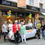 Mitwirkende am Projekt Weltladen stehen von dem Eingang. Weiter ist ein weißer Fiat Cinquecento mit einem Werbeplakat zwischen den Menschen zu sehen.