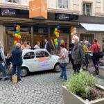 Vor dem Laden steht ein weißer Fiat Cinquecento mit einem Werbeplakat. Es sind viele Interessierte und Mitwirkende unterhalten sich.
