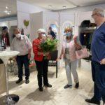 Im Laden stehen vier Personen. Ein Blumenstrauß wurde überreicht.